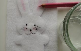 a white Fleece bunny with stitched face and pink ears