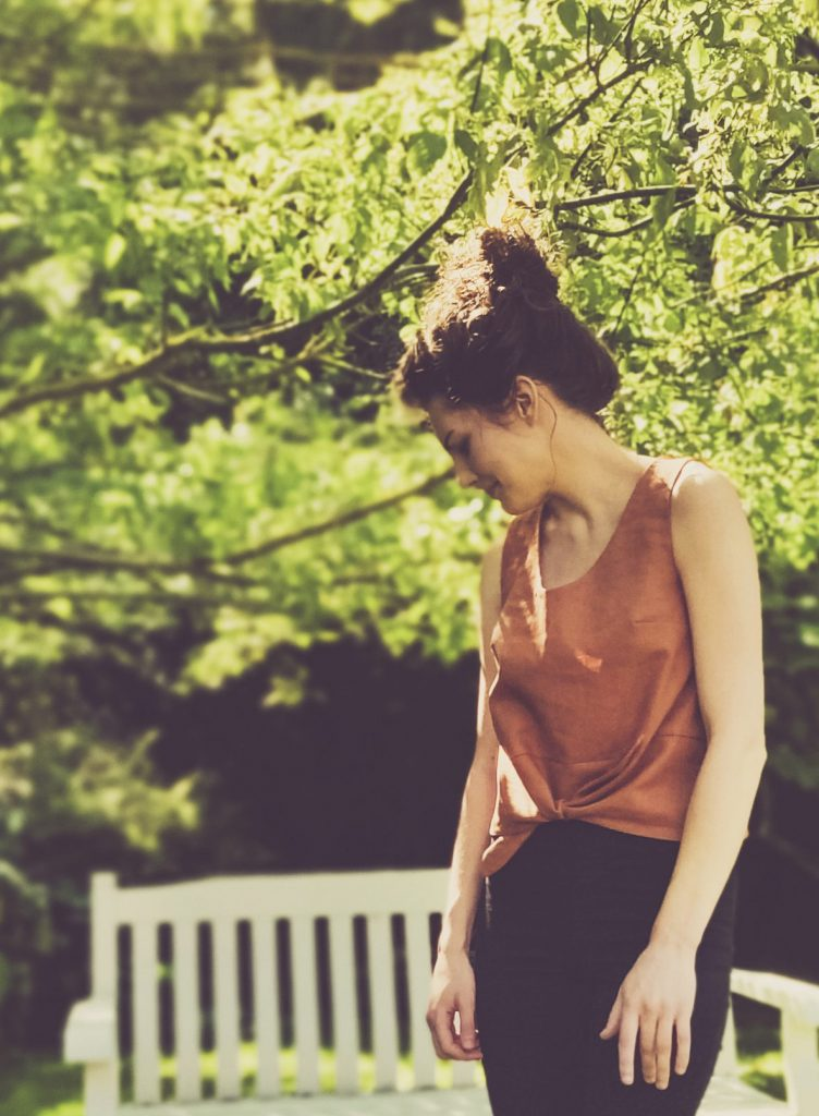 Summer girl with hair in bun wearing black skinny jeans and brown short sleeved Jily Top with a waist tie