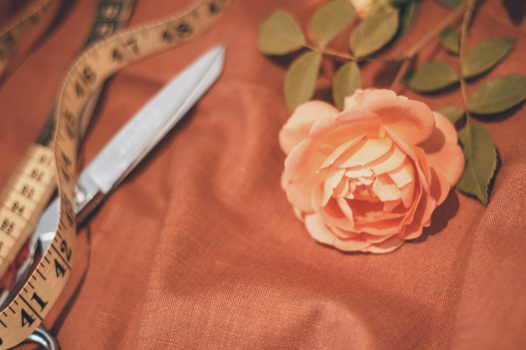 orange rose on orange brown linen with scissors and old fashioned tape measure