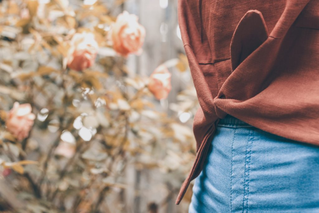 girl wearing blue skinny jeans and brown linen Jily Top waist only wit roses in garden background