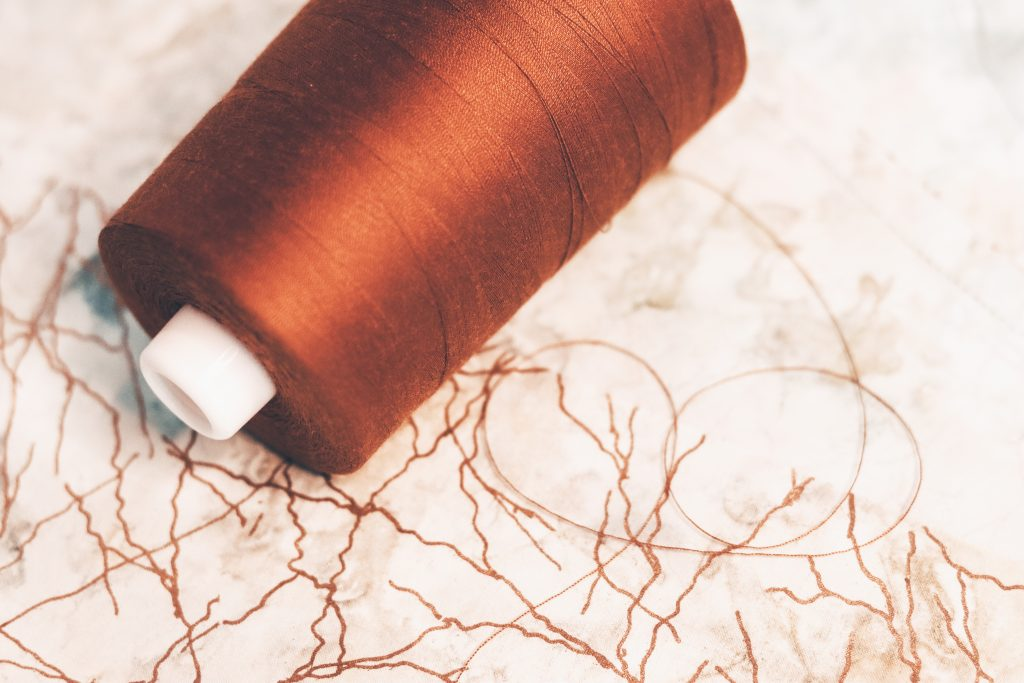 OMNI thread cone brown gold against batik fabric