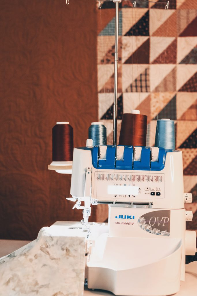 the JUKI MO-2000 QVP threaded with blue and brown threads with autumnal triangle quilt in background