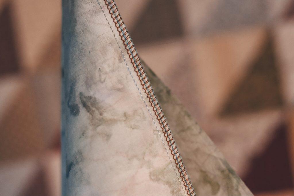 overlocked stitch on batik fabric blue and brown threads