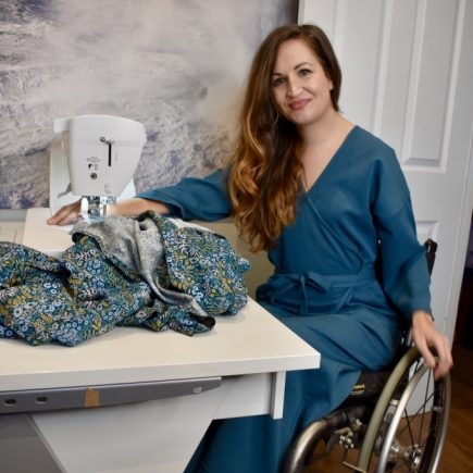 Marie Lawlor Juki Ambassador sitting in a teal wrap dress in her wheelchair in front of her Juki NX7 sewing machine on an RMF table