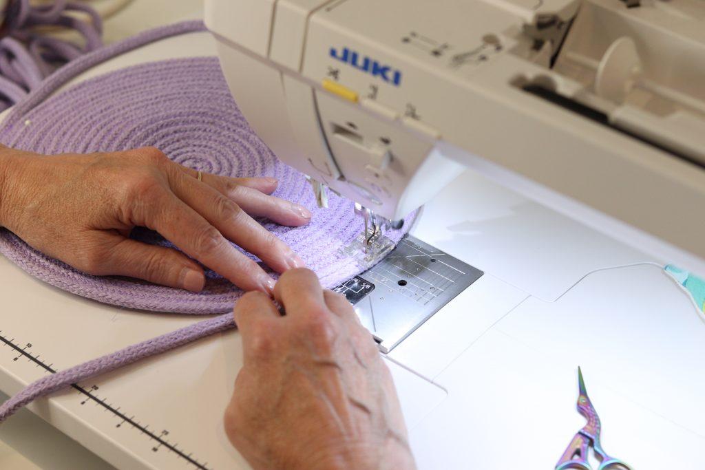 stitching a light purple rope bag